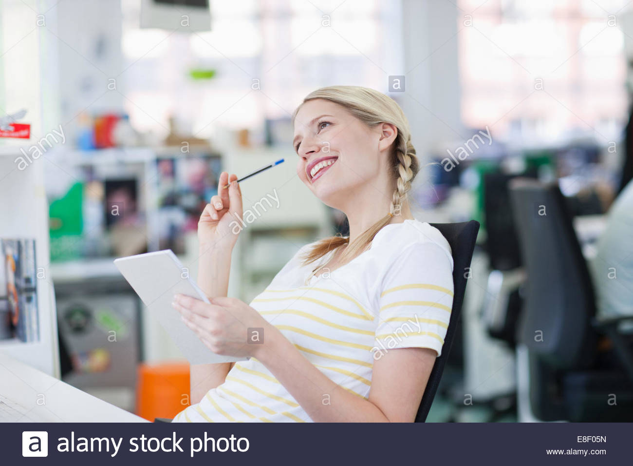 Smiling businesswoman holding notepad and looking up in office - Stock Image