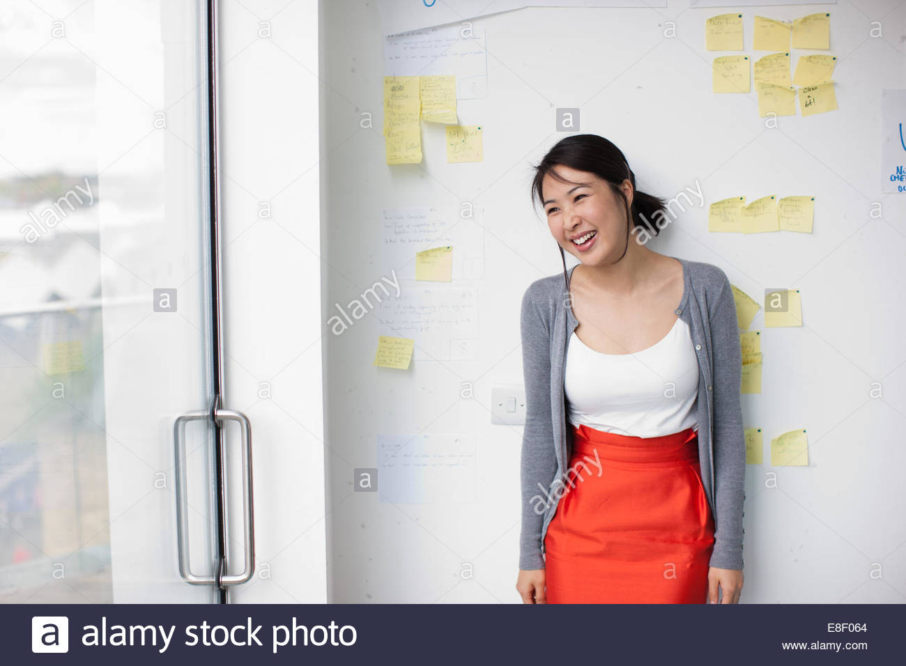 Smiling businesswoman with in front of whiteboard with adhesive notes - Stock Image