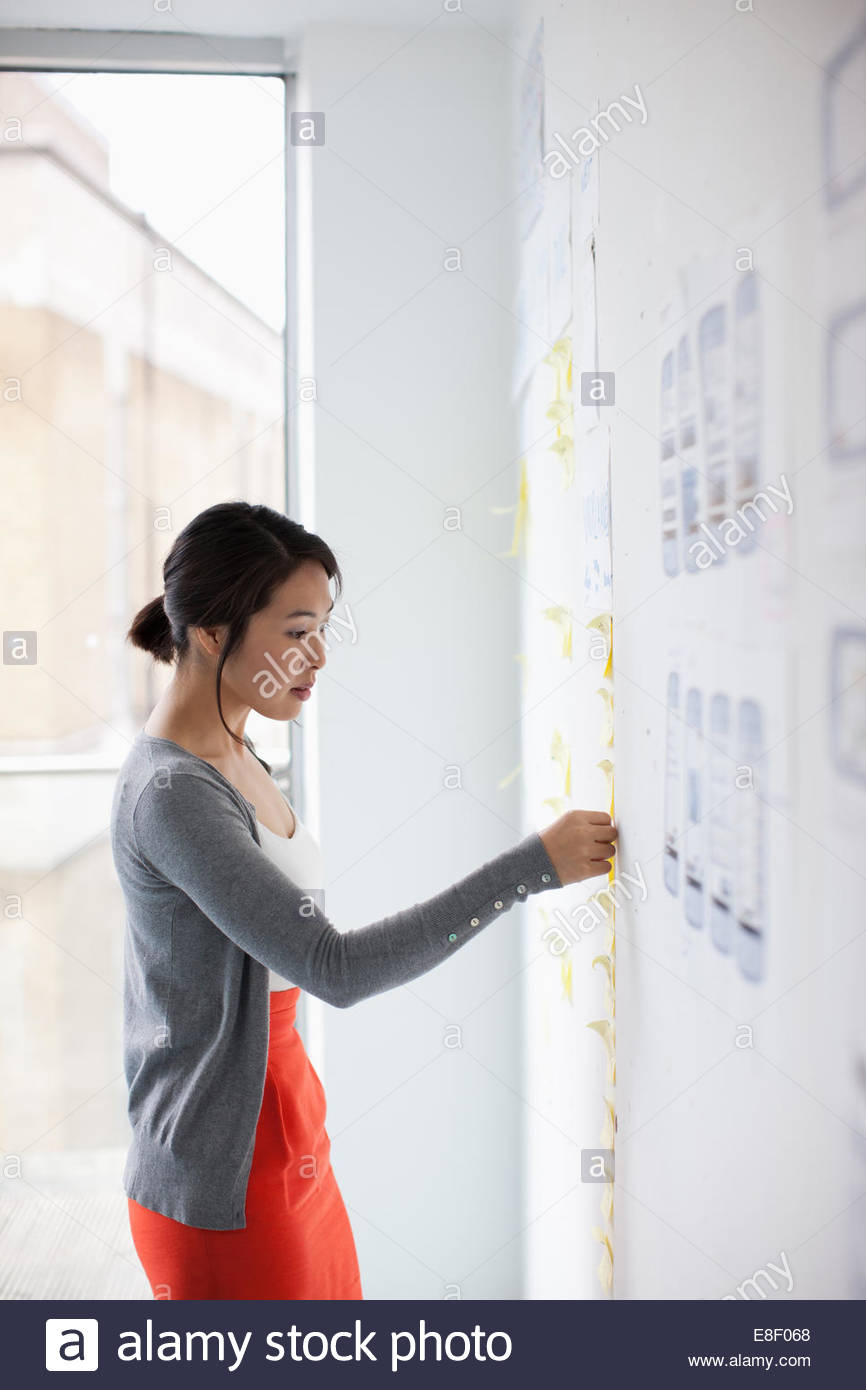 Businesswoman placing adhesive note on whiteboard - Stock Image