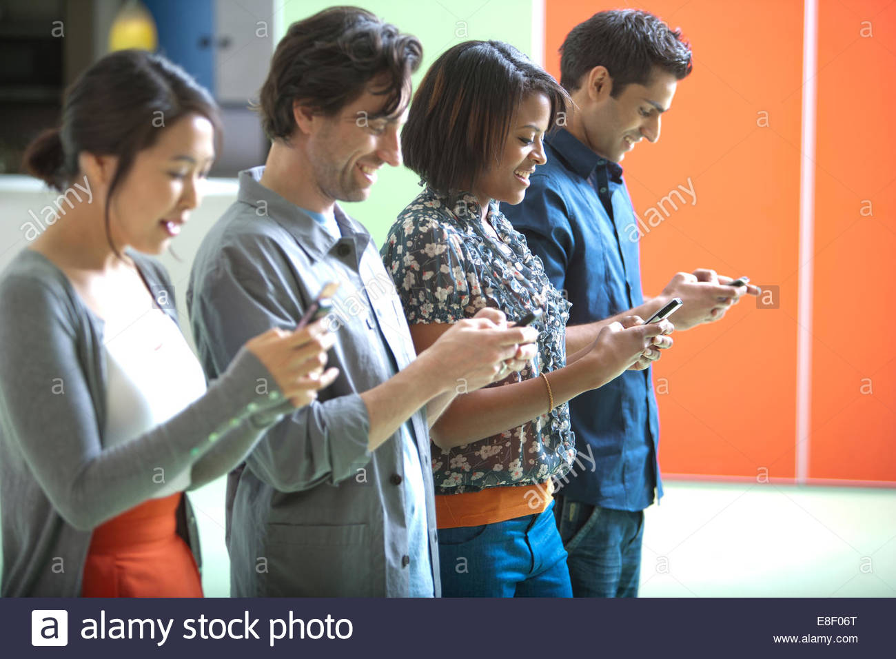Smiling men and women text messaging on cell phones in a row - Stock Image