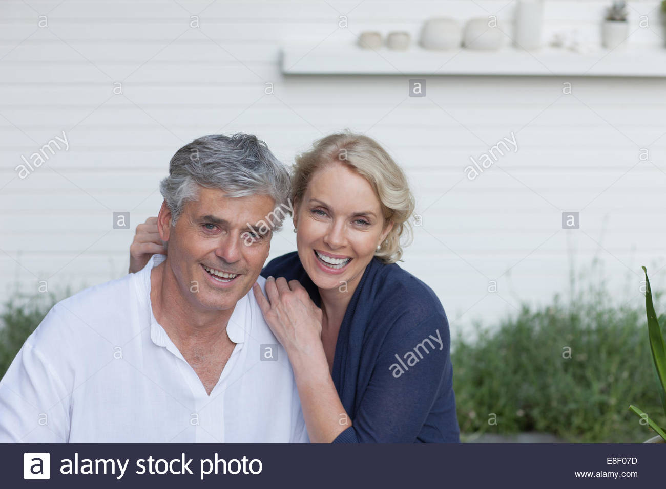 Smiling couple hugging outdoors - Stock Image