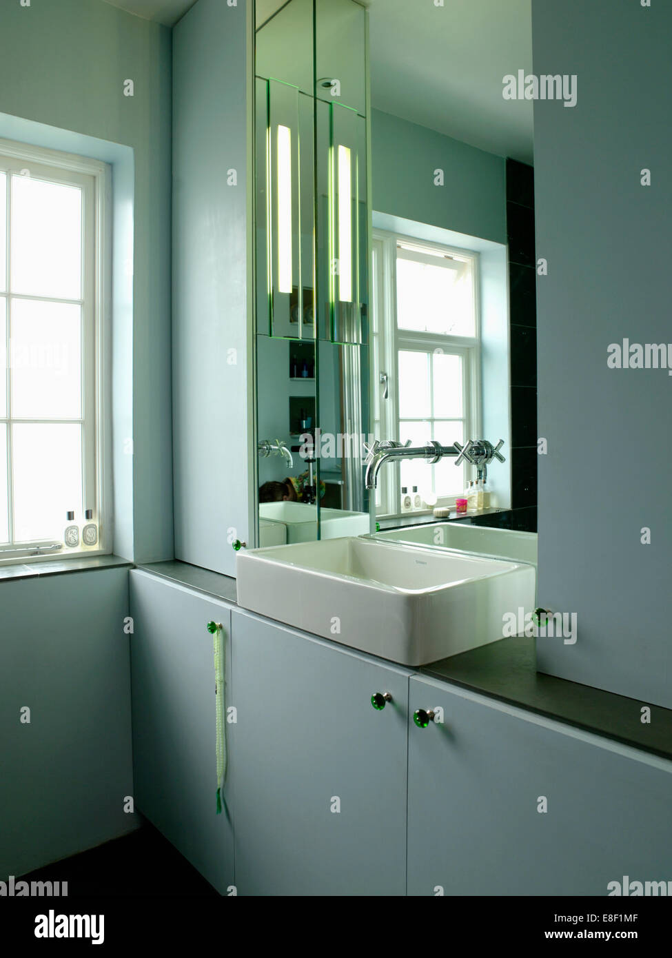 Lighting on mirror above ceramic basin on vanity unit in pale gray ...