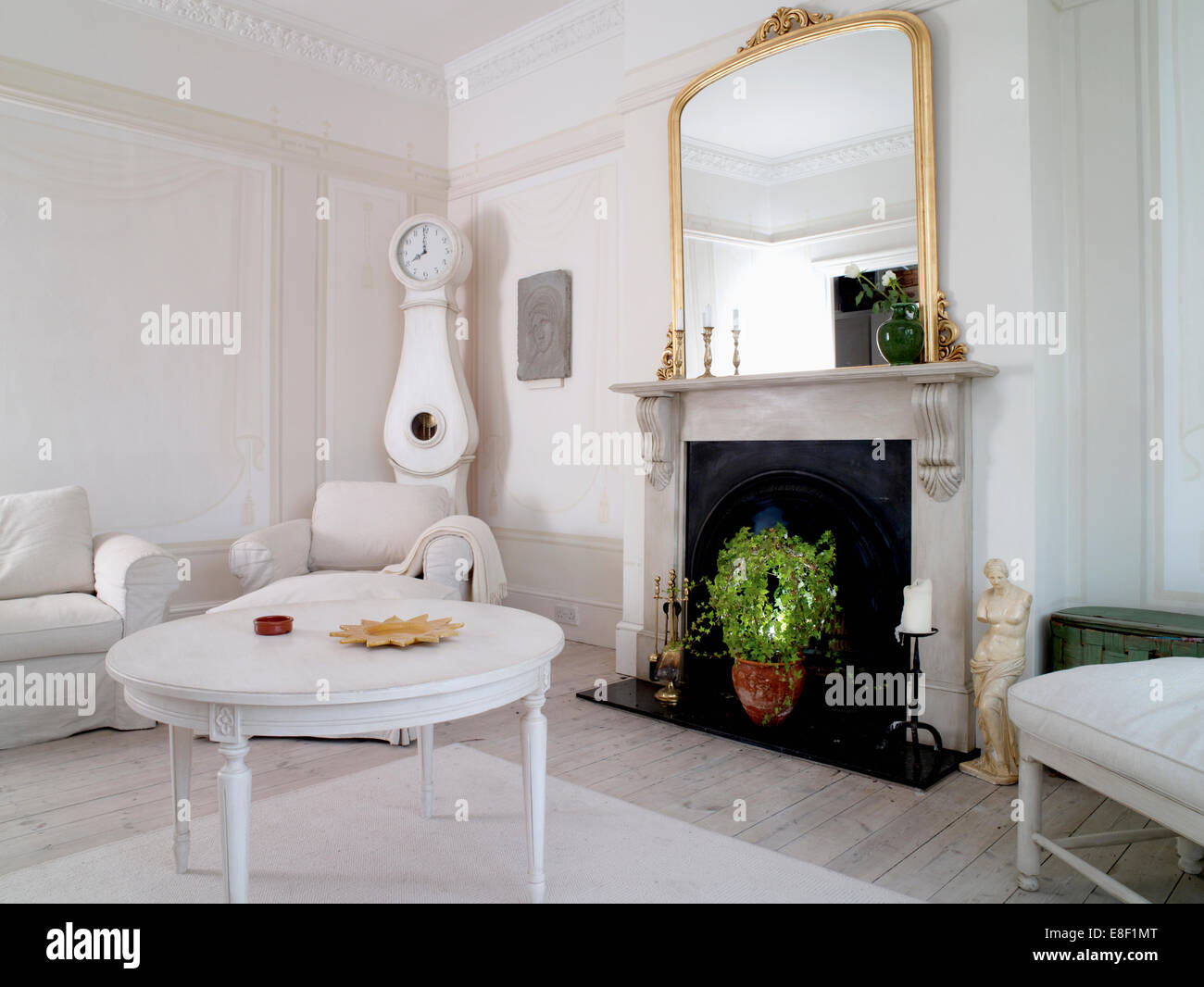 White painted coffee table in front of marble fireplace with large ...