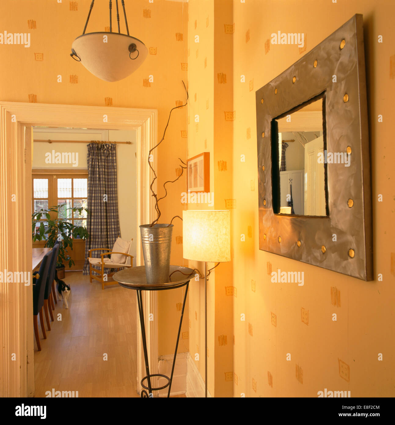 Metal framed mirror and plant stand in small modern hall with ...