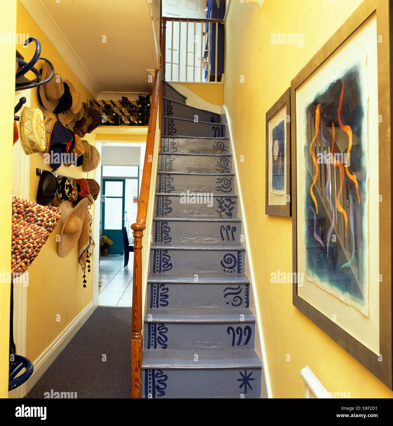 Hand-painted gray wooden staircase in yellow hall with collection of ...