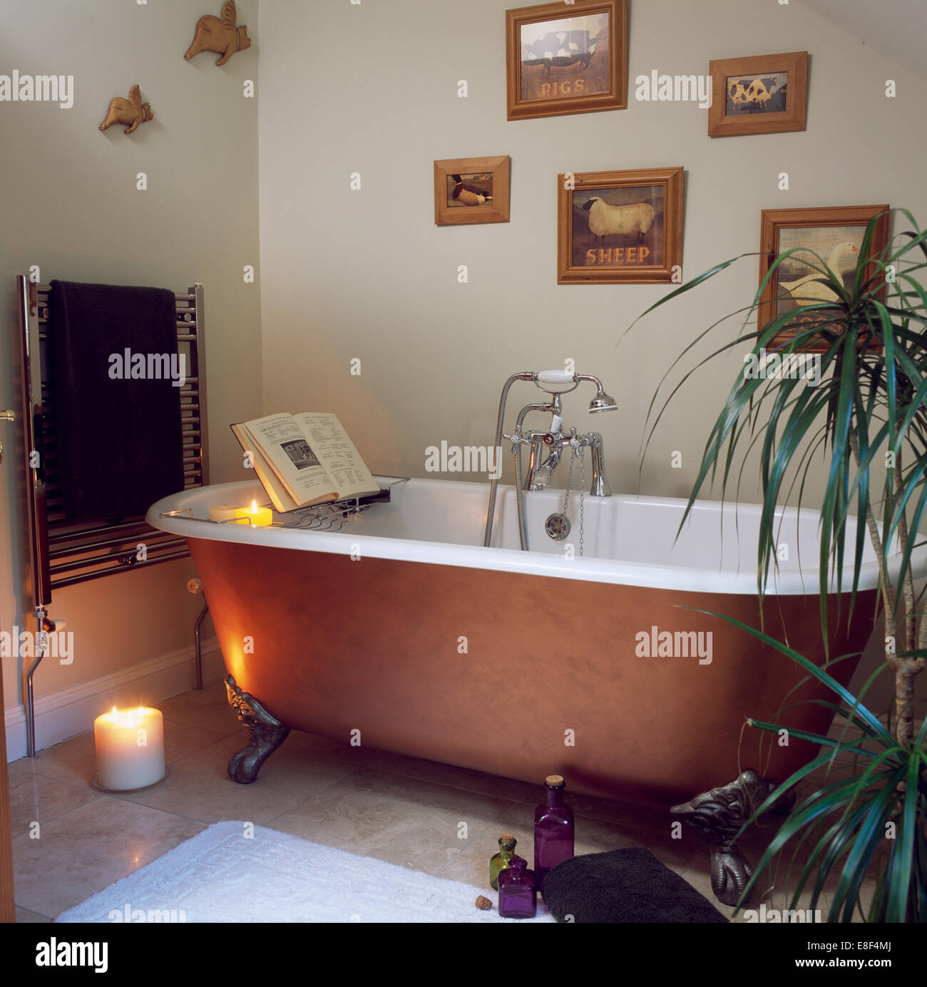Lighted candle on floor in traditional bathroom with book propped on ...