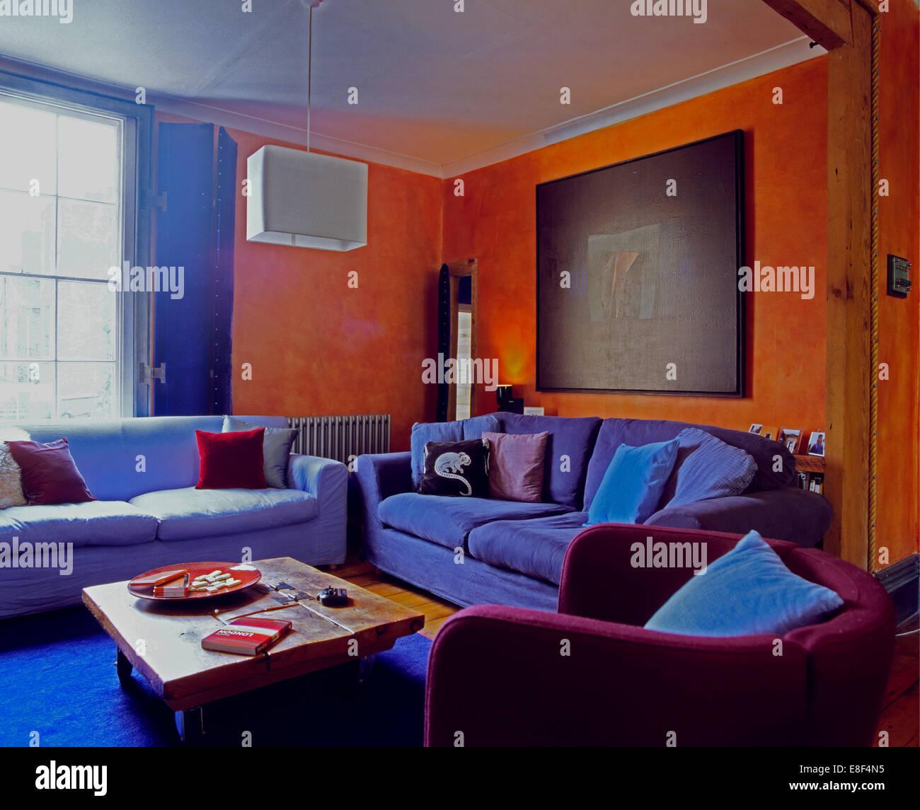 Blue velvet sofas and purple armchair in nineties orange ...