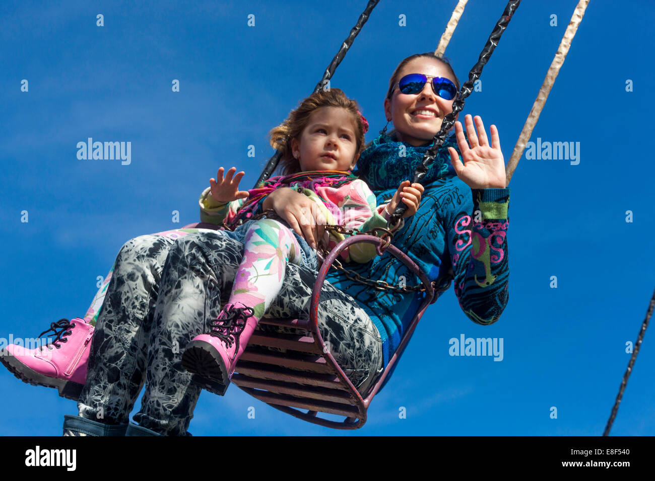 mother with daughter  on the chain swing carousel, amusement park - Stock Image
