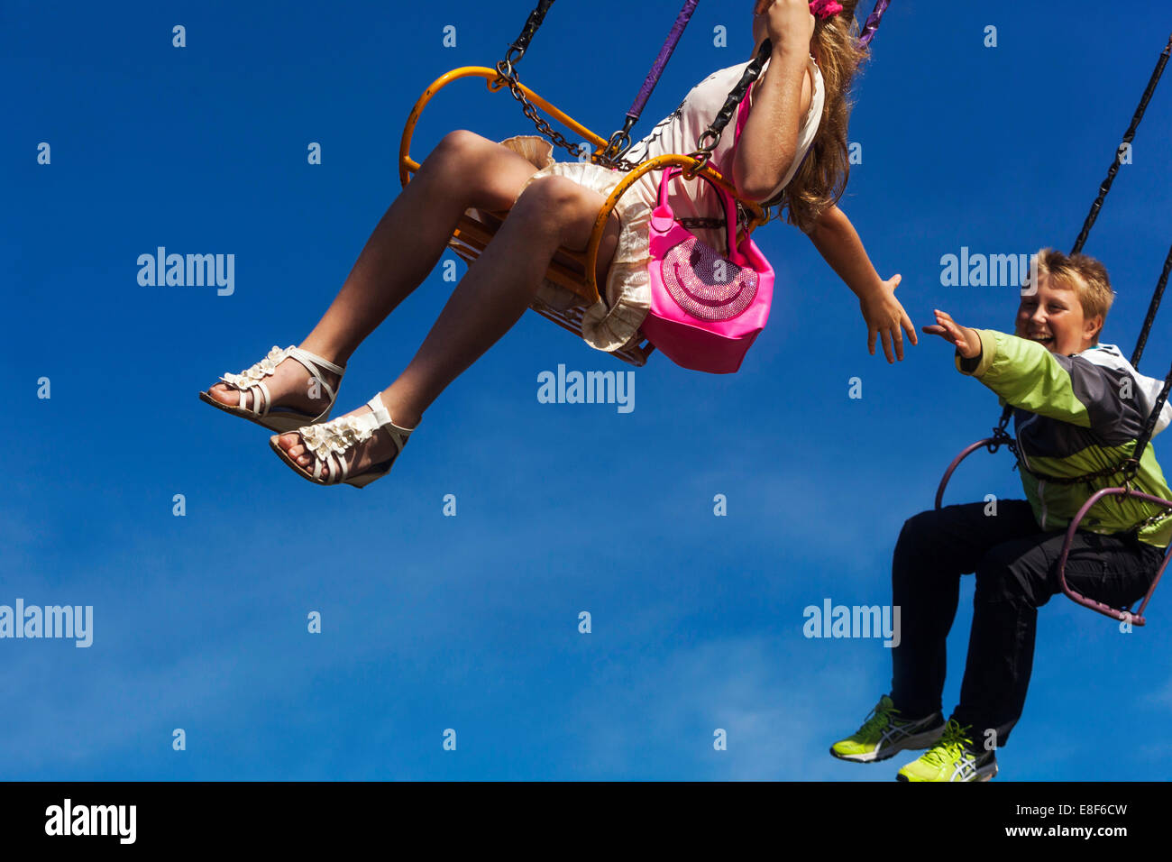 young people on the chain swing carousel, village fair, Czech Republic - Stock Image