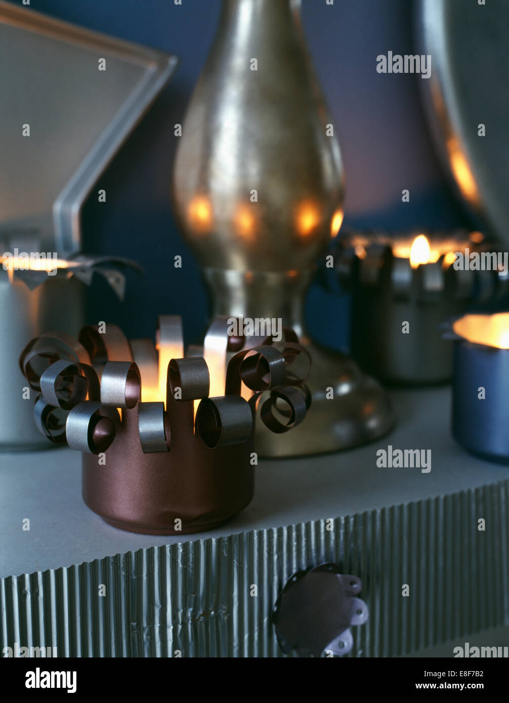 Close-up of lighted tea lights in candle holders made from old tins - Stock Image