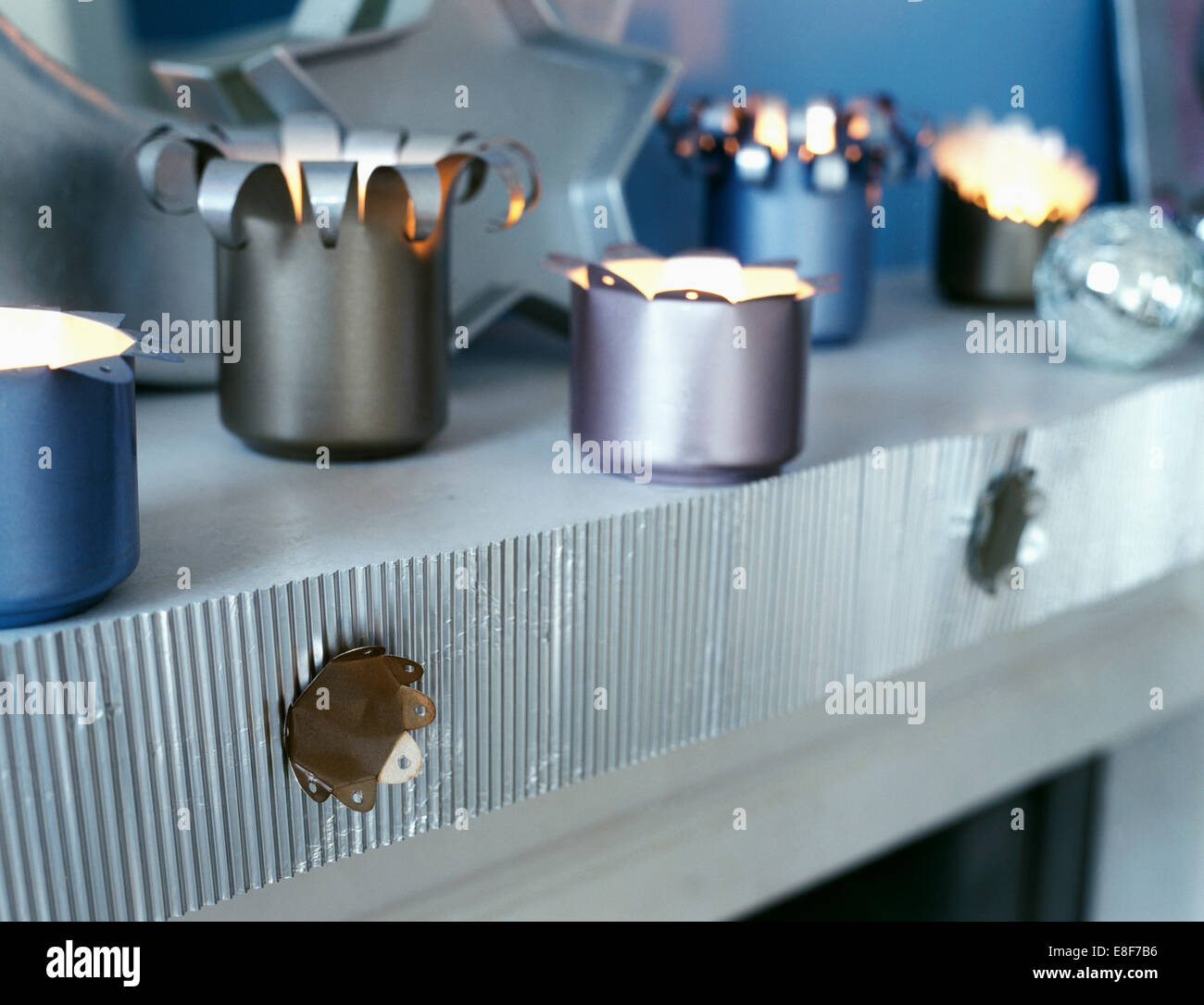 Close-up of lighted tea lights in candle holders made from old tins on shelf with silver corrugated card trim - Stock Image