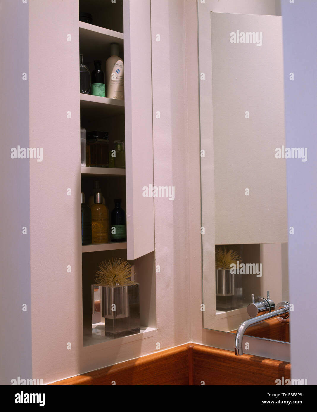 Close Up Of Bathroom Cupboard With Door Open To Reveal Toiletries On Shelves Beside Mirror And Chrome Tap