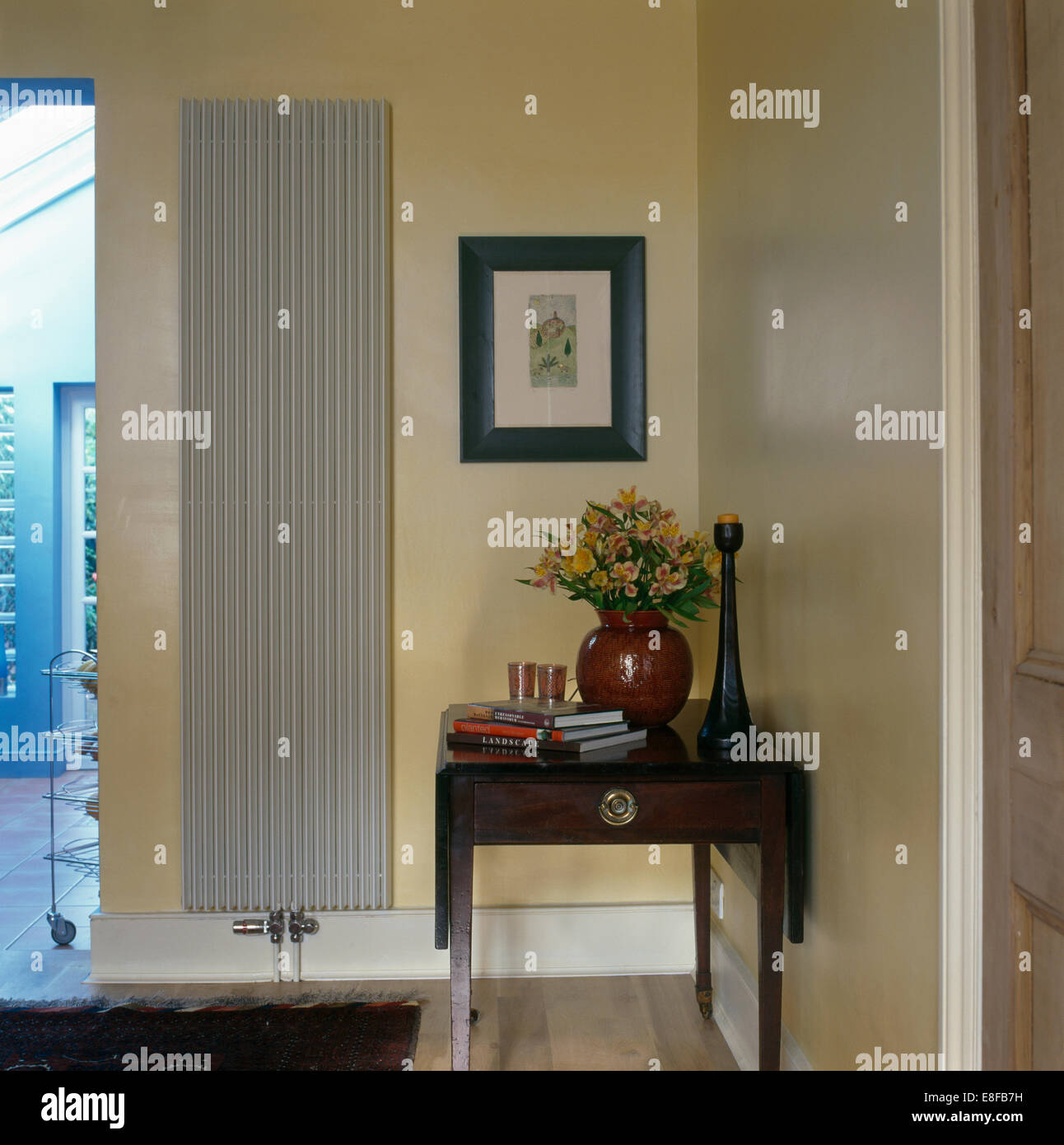 Vertical Radiator On Wall Beside Small Antique Table In