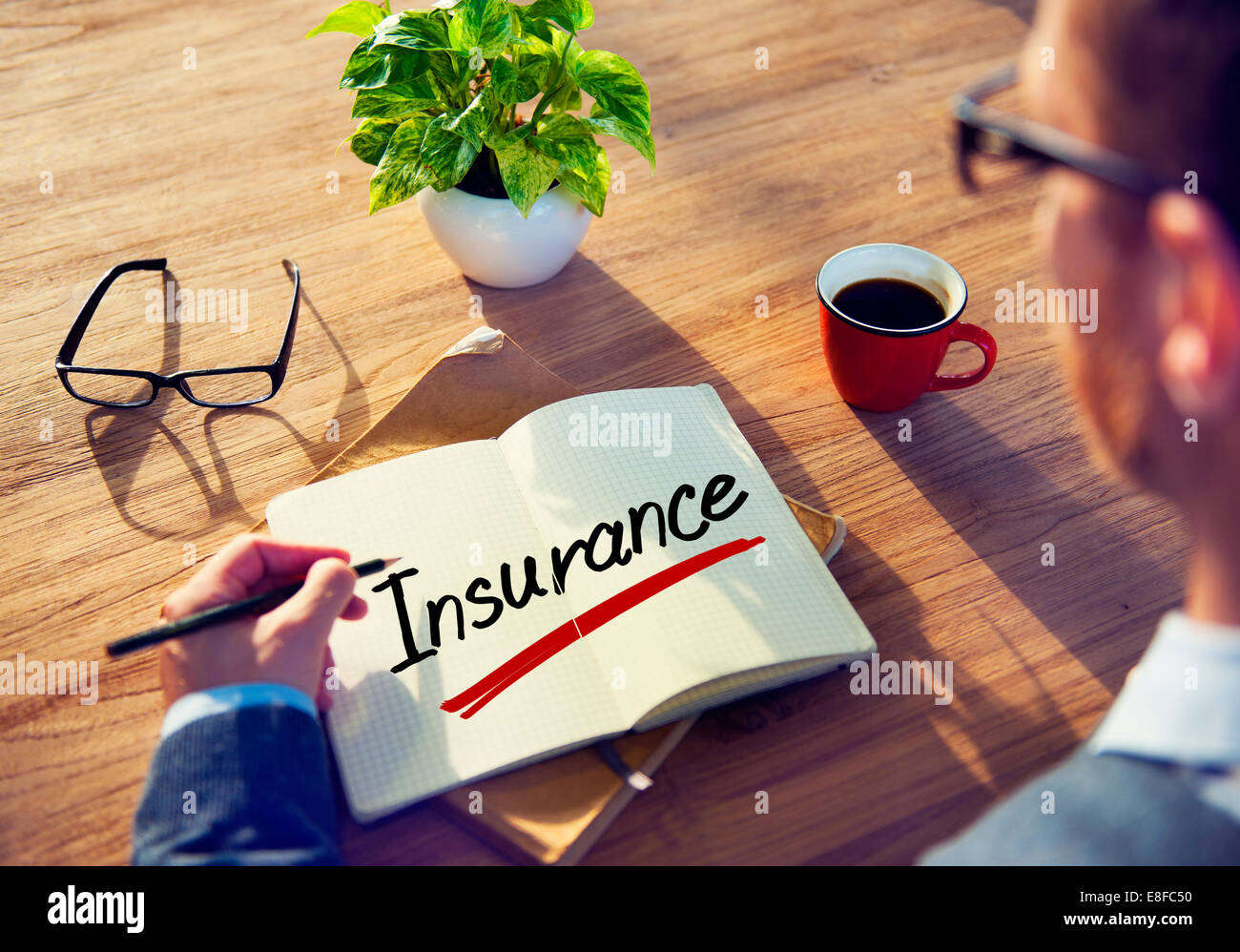 Man with a Note and a Single Word Insurance - Stock Image