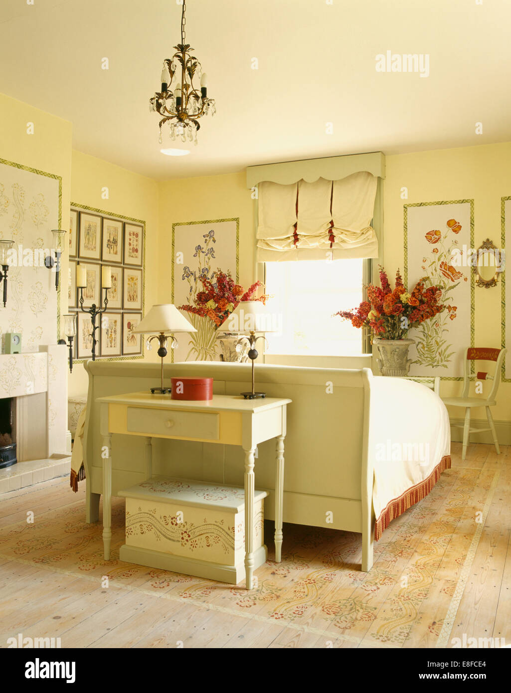 Cream painted table and bed in country bedroom with stenciled wall ...