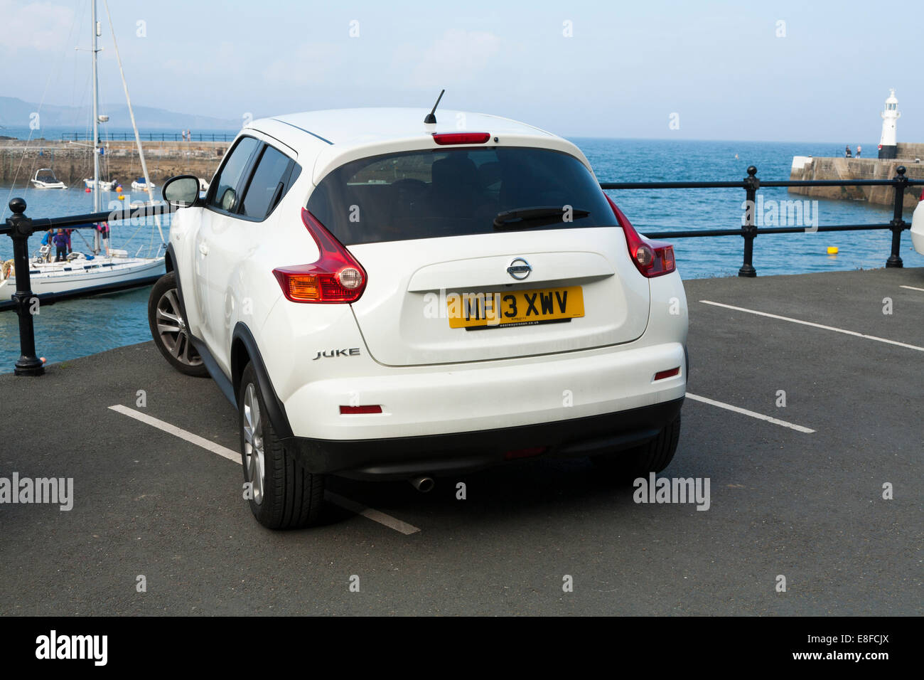 Nissan Juke car that's not been parked within the constraints of a parking space / white markings / bay, so - Stock Image