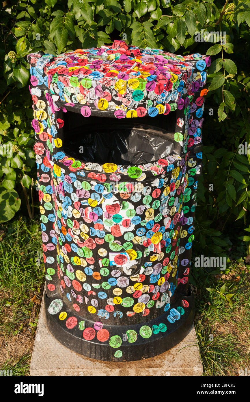 Litter bin covered in self adhesive stickers / sticker decorated, decorative rubbish bins in Mevagissey Cornwall - Stock Image