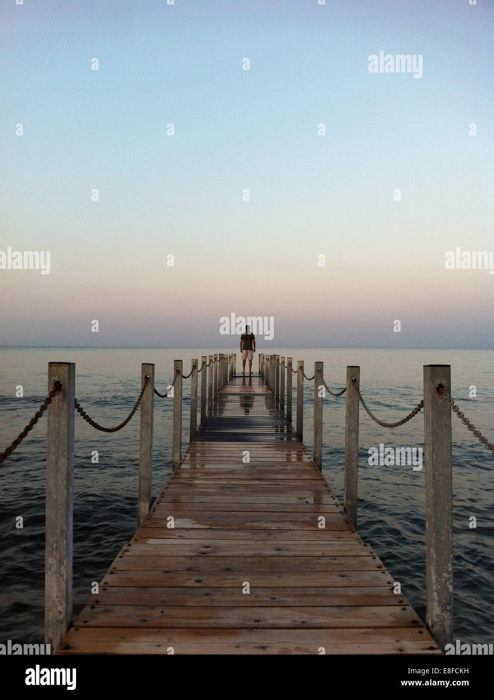 Man standing at the end of pier, Attica Periphery, Greece - Stock Image