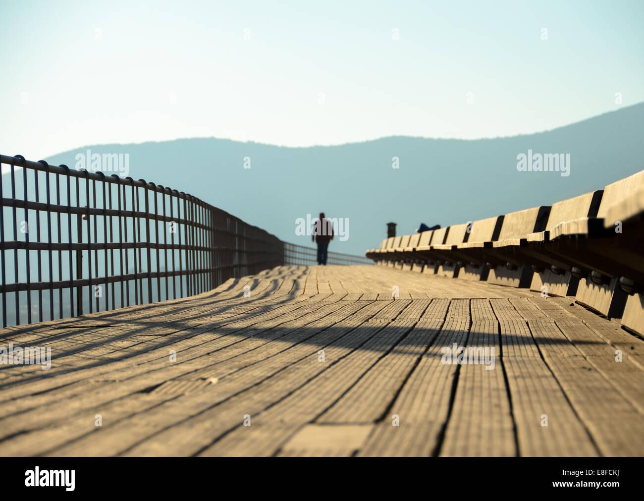 Greece, Attica Periphery, Porto Rafti, Person walking through wooden footbridge - Stock Image