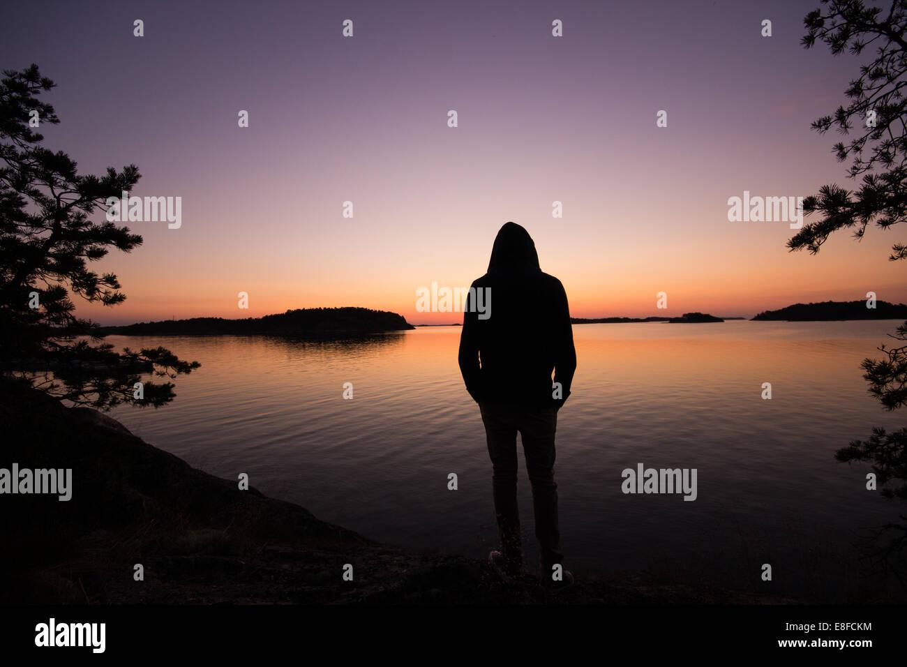 Man looking out at lake - Stock Image