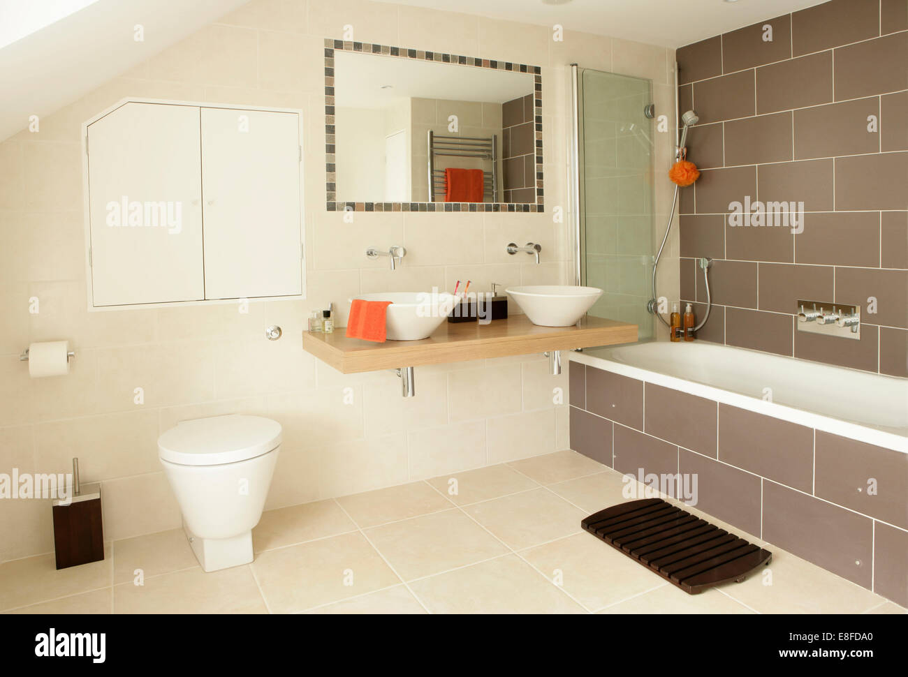 Tiled-framed mirror above white bowl basins on wooden vanity shelf ...