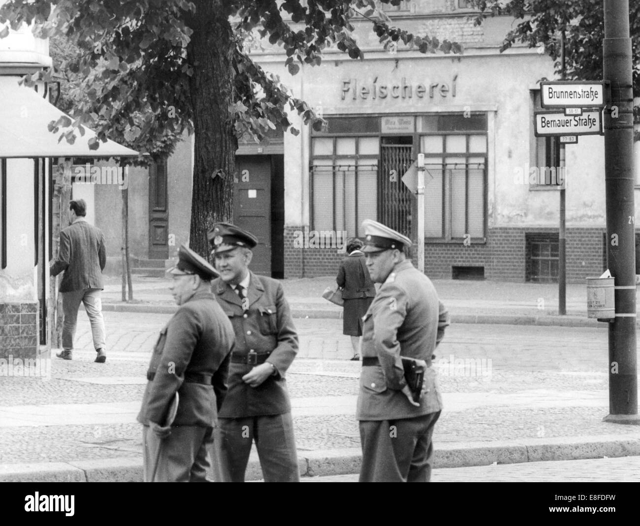 Policemen in West Berlin and customs officers not far away from a closed bucher's shop in Bernauer Street in Berlin, 7 July 1961. The shop belongs to East Berlin, the Western part of the city begins from the pavement in front of the shop. From 13 August 1961, the day of the building of the Berlin Wall, until the fall of the Berlin Wall on 9 November 1989, the Federal Republic of Germany and the GDR were separated by the Iron Curtain between West and East. Stock Photo