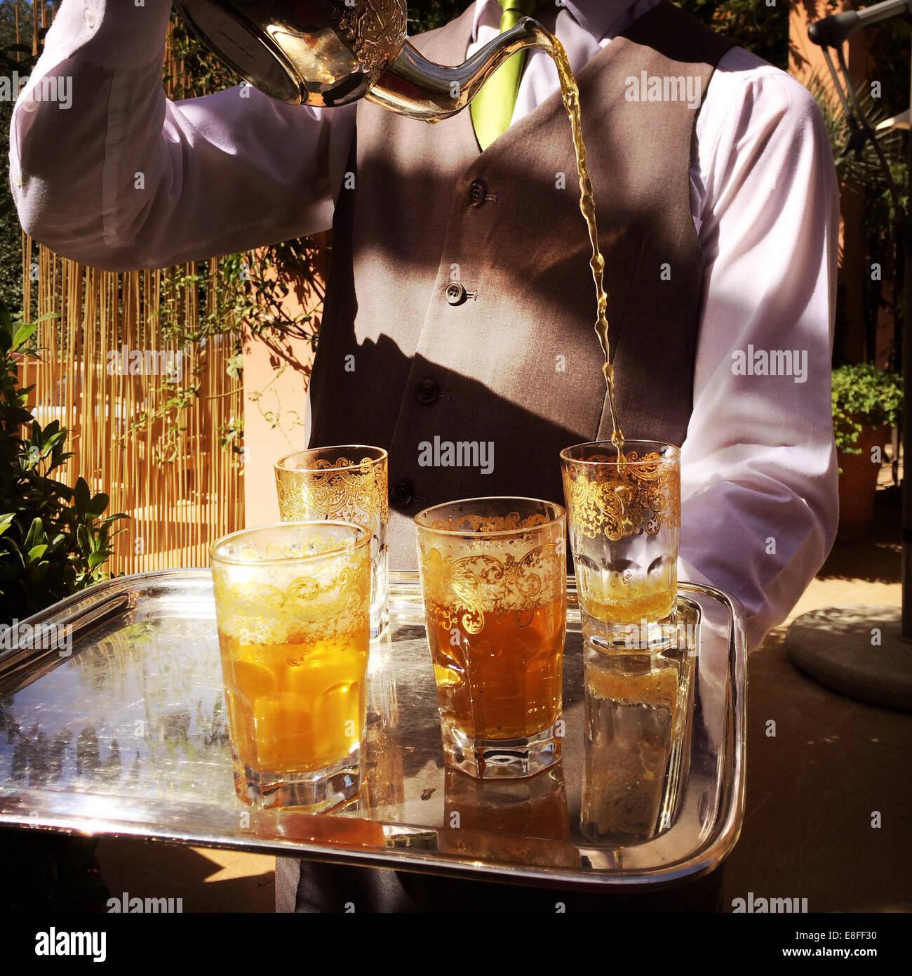Morocco, Marrakesh, Waiter pouring tea during tea ceremony - Stock Image