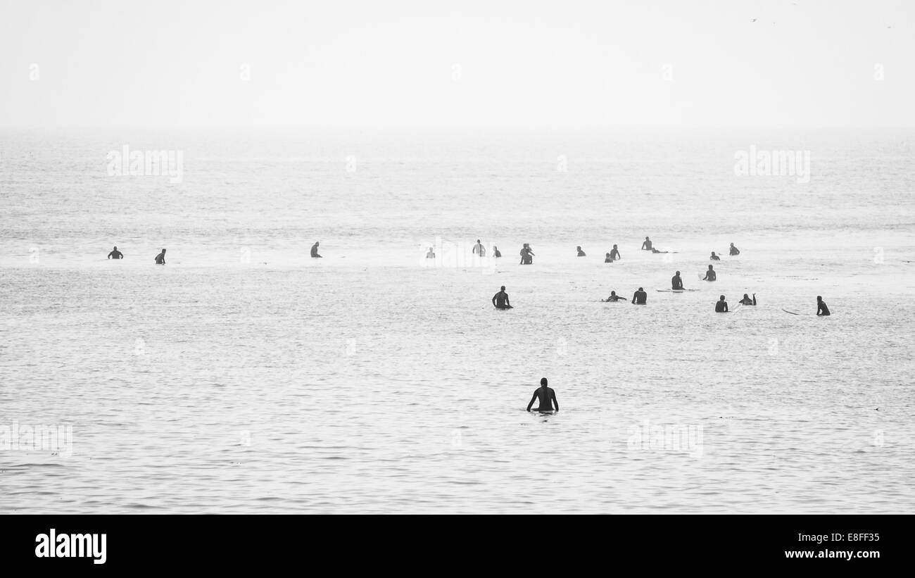 Large group of surfers in ocean waiting to catch a wave - Stock Image
