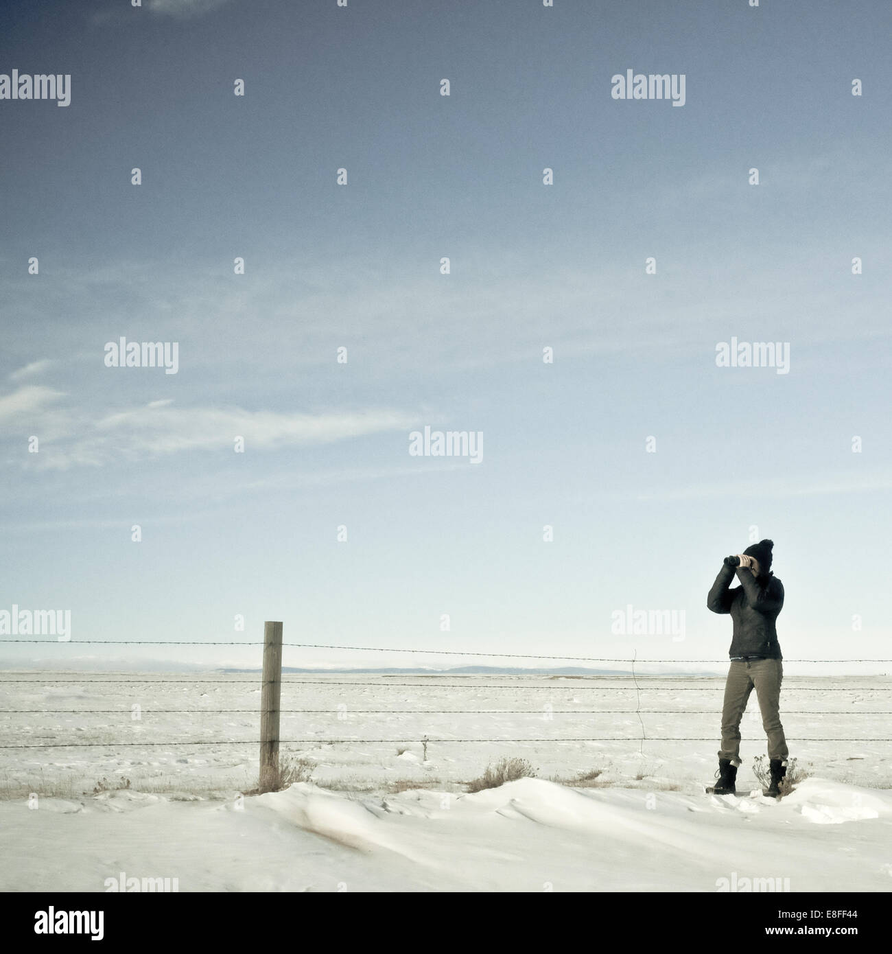 woman looking through binoculars in winter, Wyoming, America, USA - Stock Image