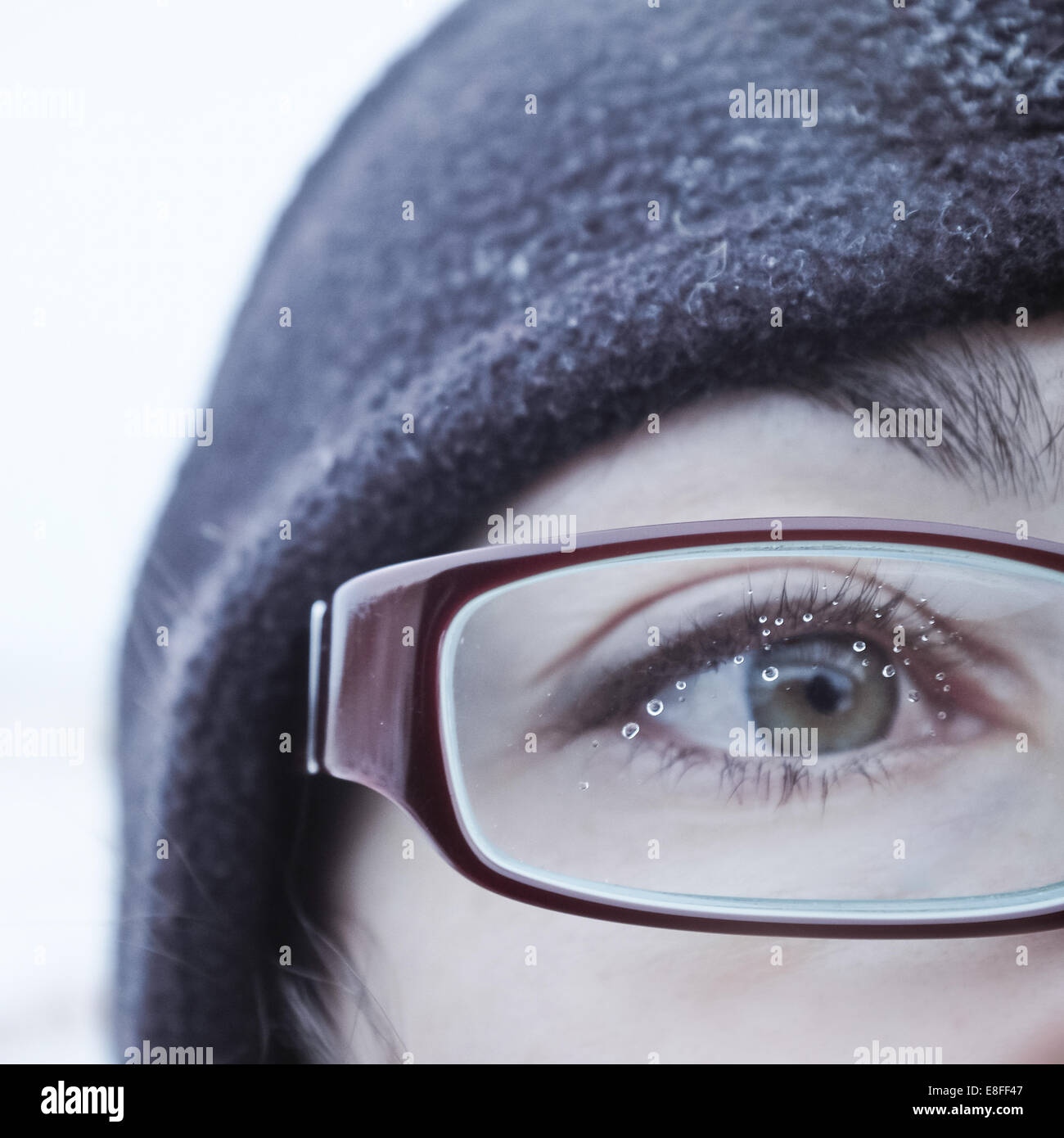 Water drops on a woman's spectacle glasses - Stock Image