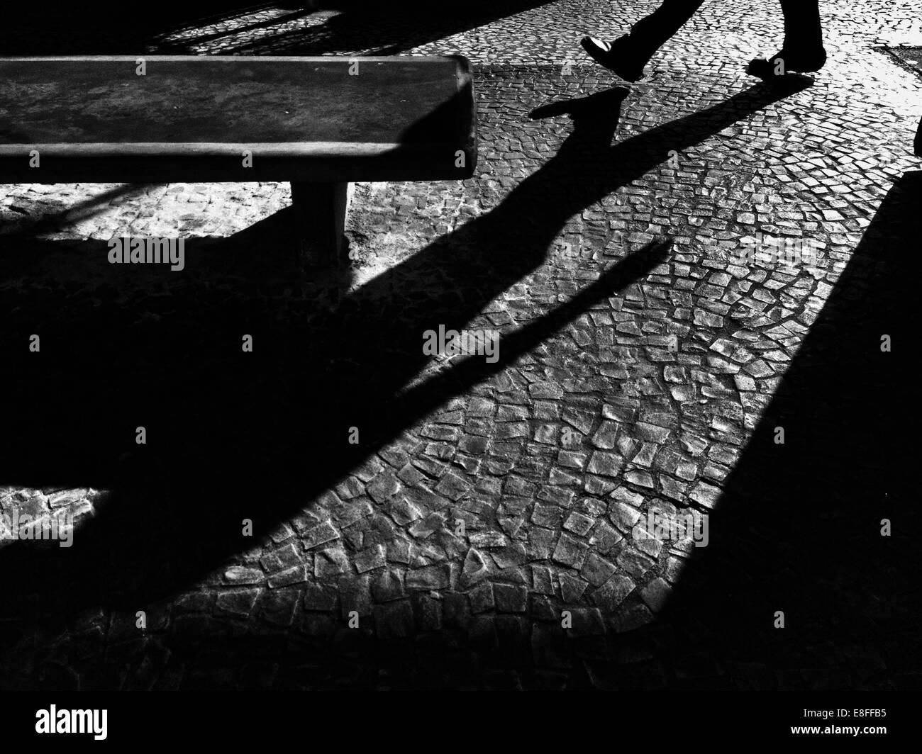Shadow of man on street - Stock Image