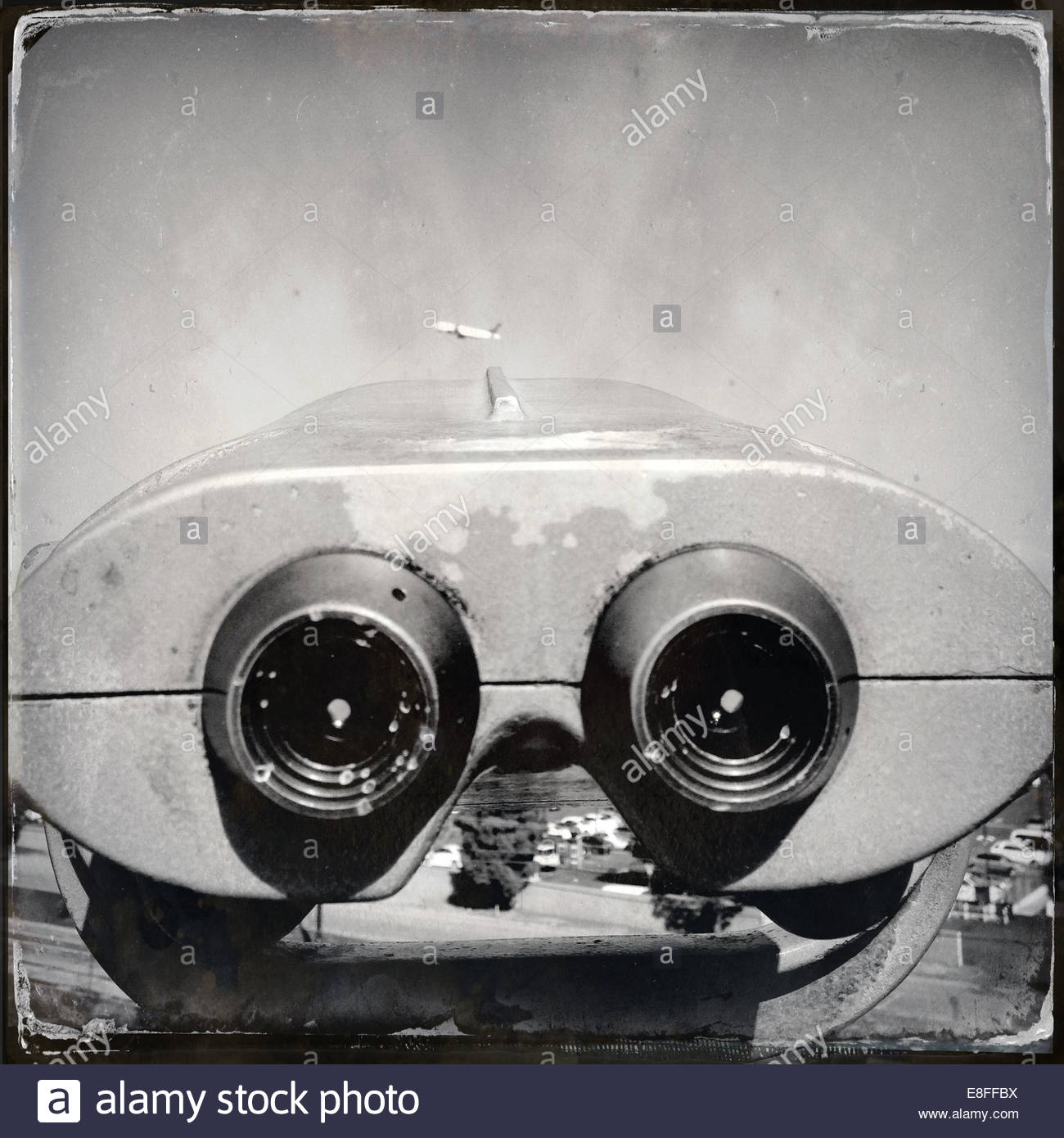 Close-up of coin operated binoculars looking towards airplane - Stock Image