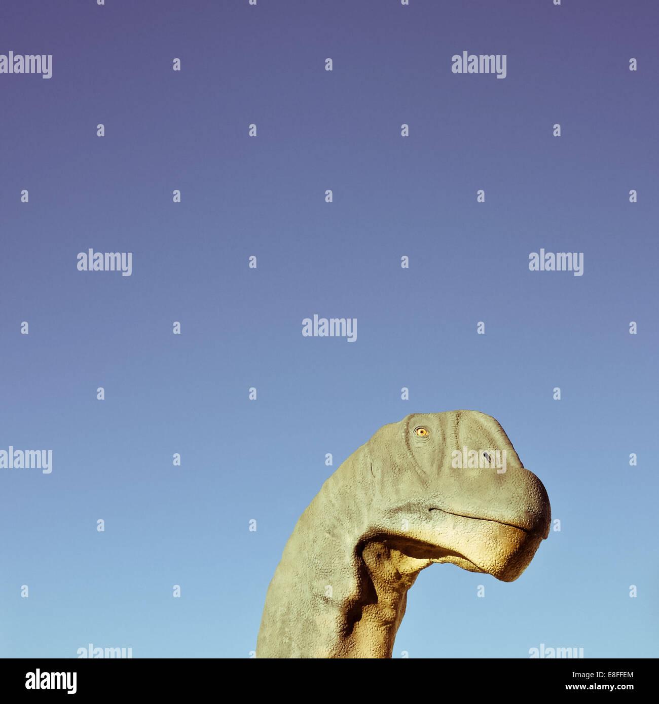 Dinosaur head against clear sky - Stock Image