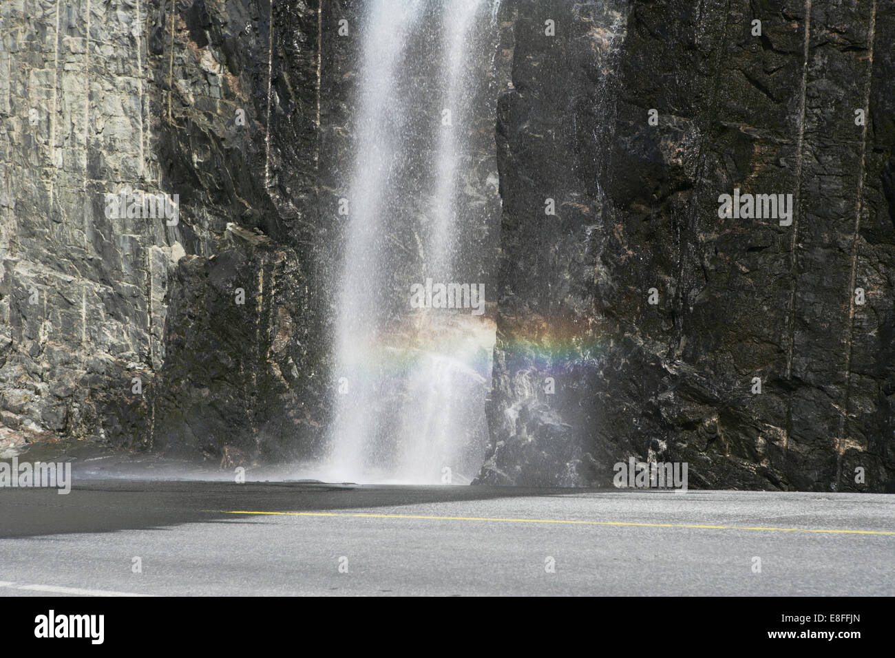Rainbow in flowing water by road - Stock Image