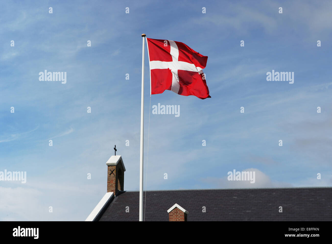 Danish flag and church against sky, Sonderho, Fanoe, Denmark - Stock Image