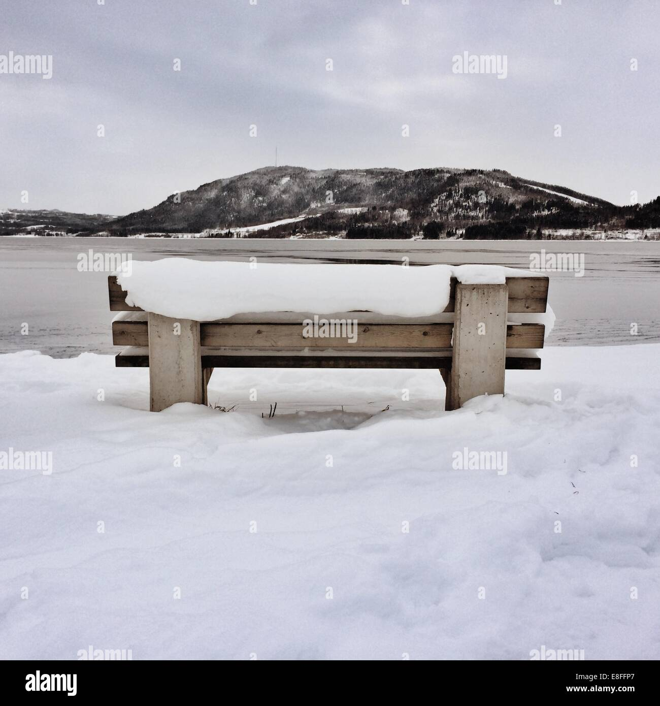 Snow covered bench by fjord, Norway - Stock Image