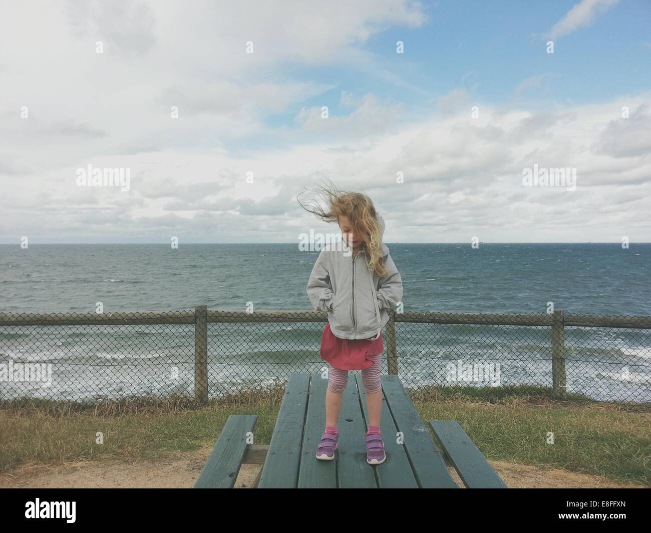 Girl standing on a picnic table by the sea - Stock Image