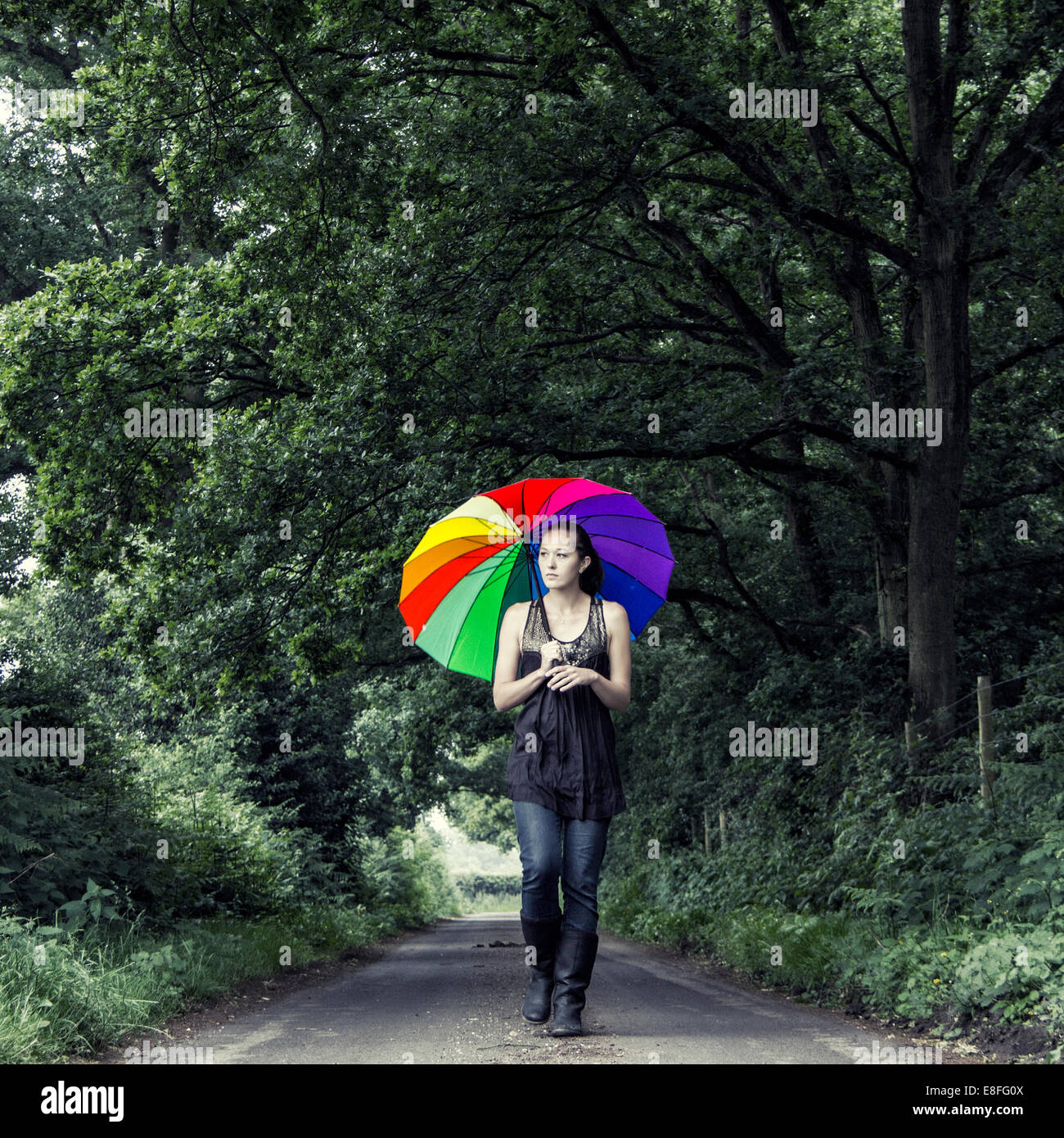Woman walking down street with multi-colored umbrella Stock Photo