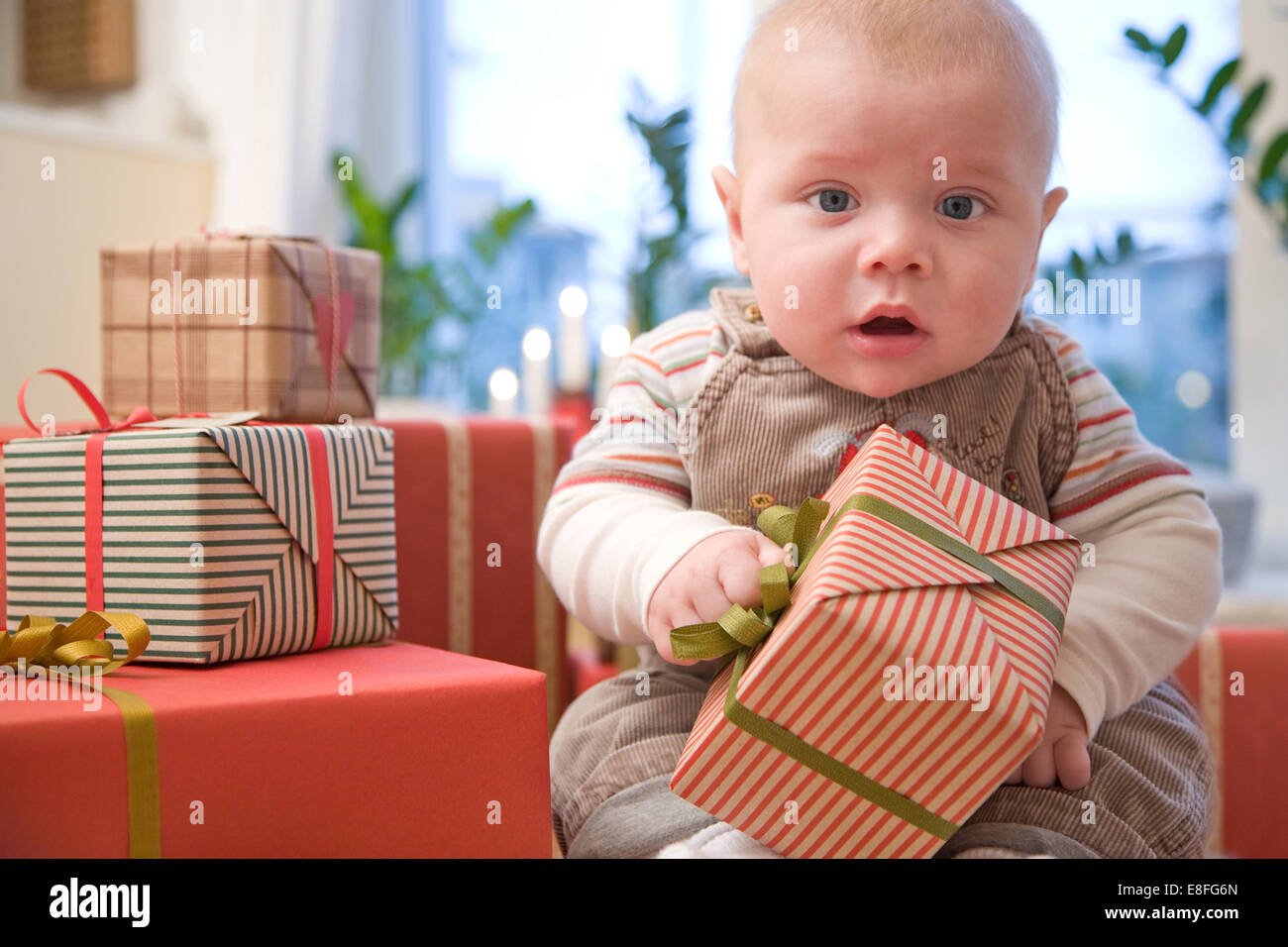 Baby boy with Christmas presents - Stock Image