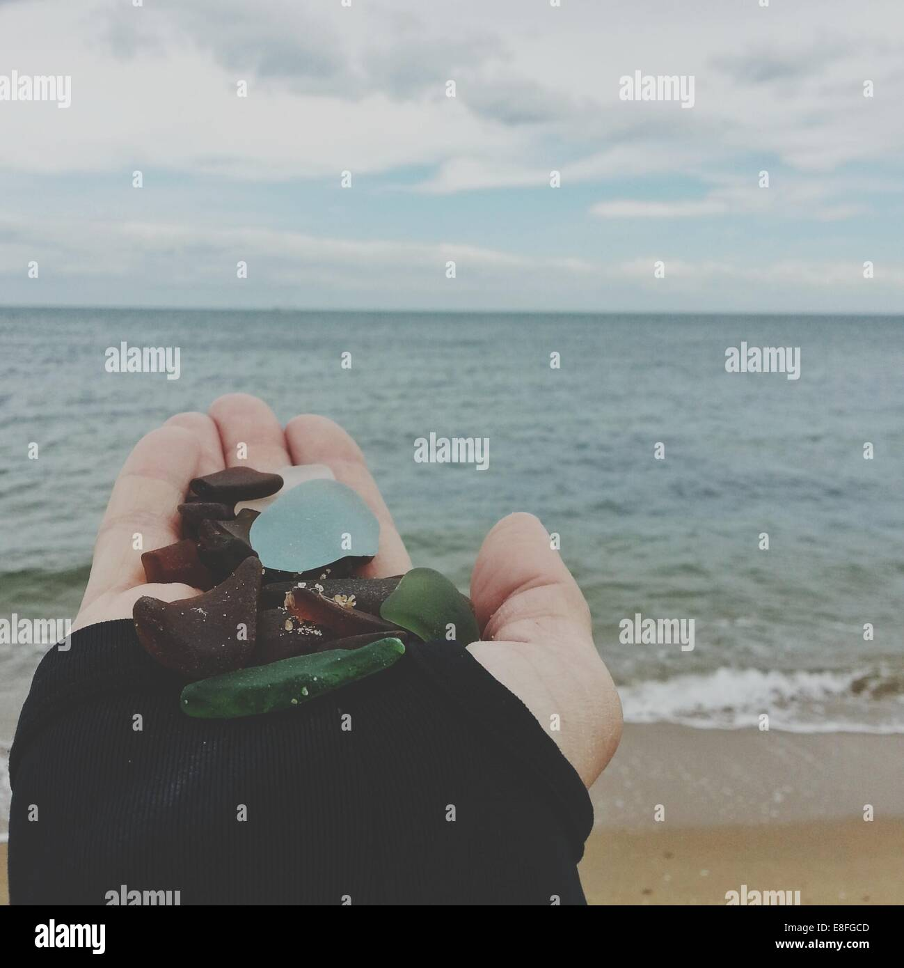 Woman's hand holding pebbles on beach - Stock Image