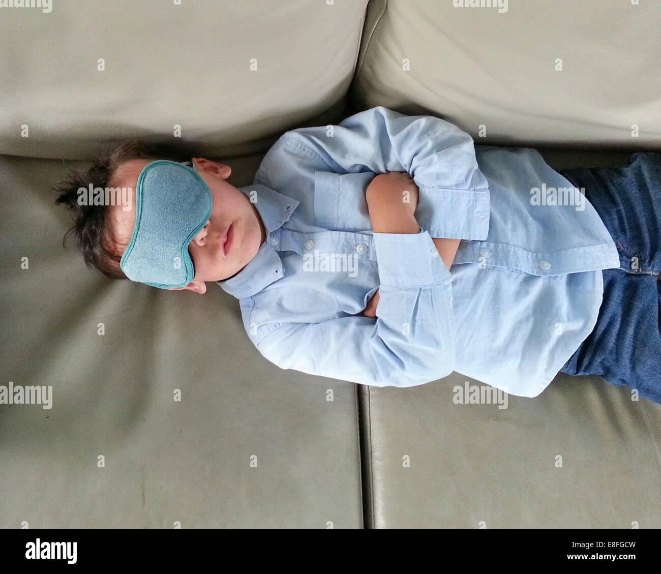 Boy lying on sofa and wearing sleeping eye mask - Stock Image