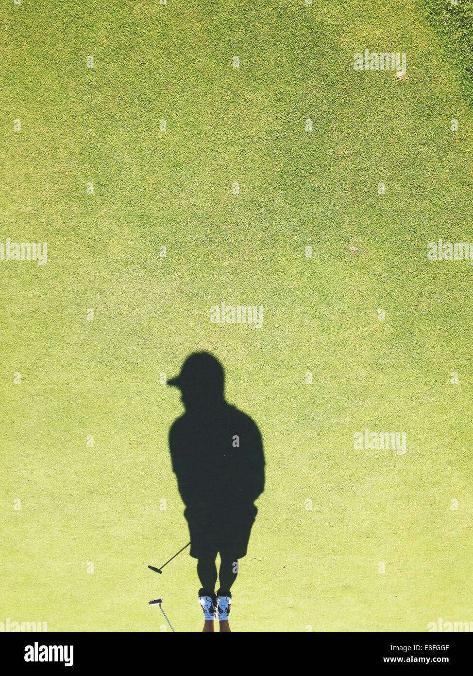 Shadow of man playing golf - Stock Image