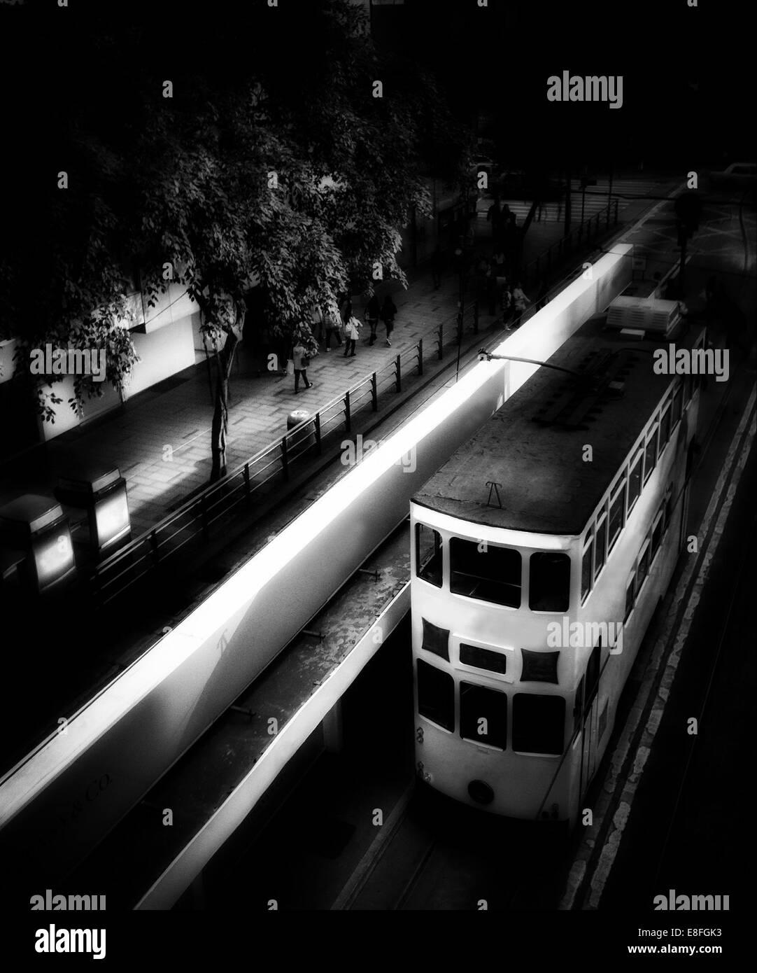Tram driving through city at night, Hong Kong, China - Stock Image