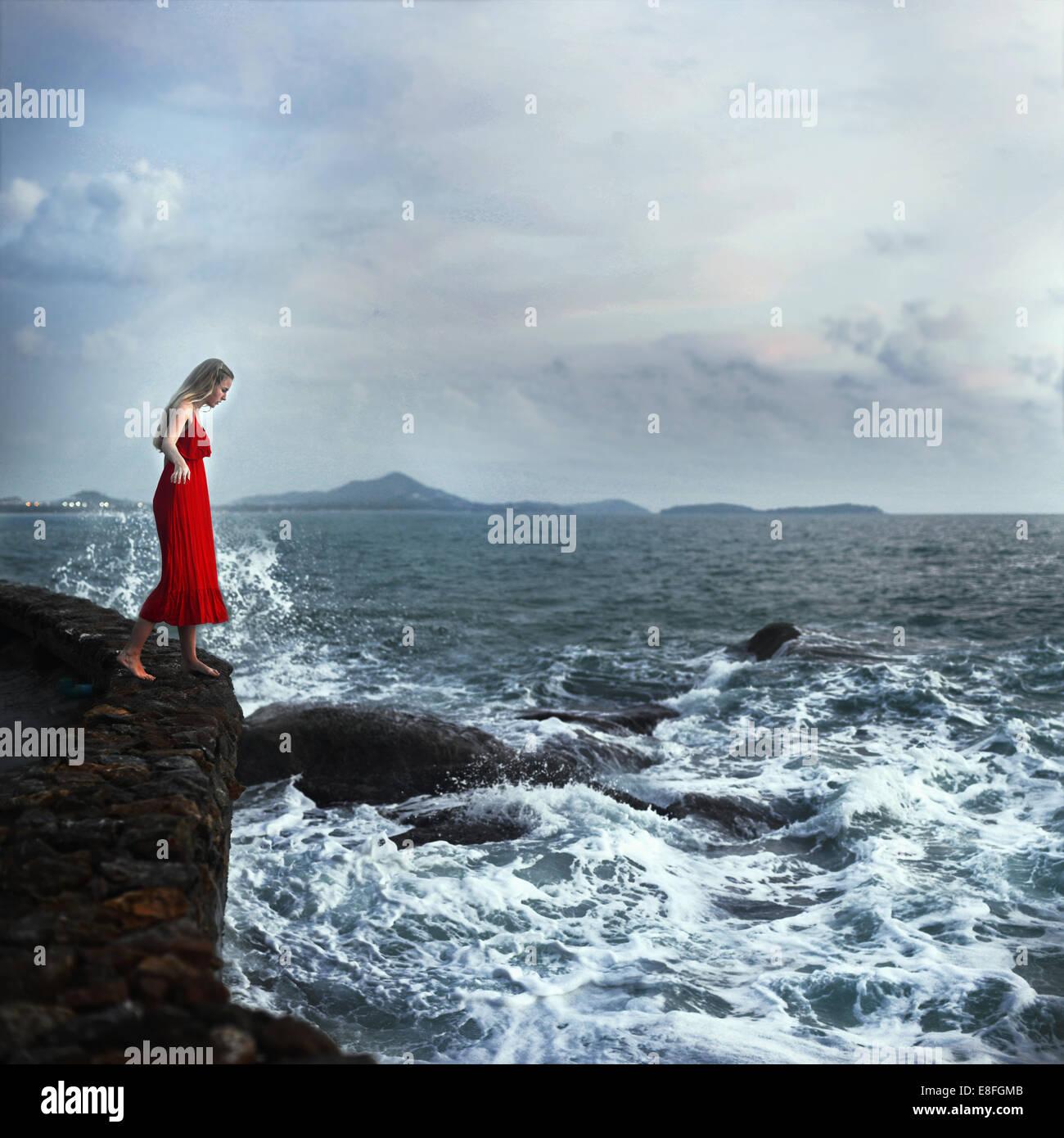 Woman standing on edge of cliffs, Koh Samui, Thailand - Stock Image