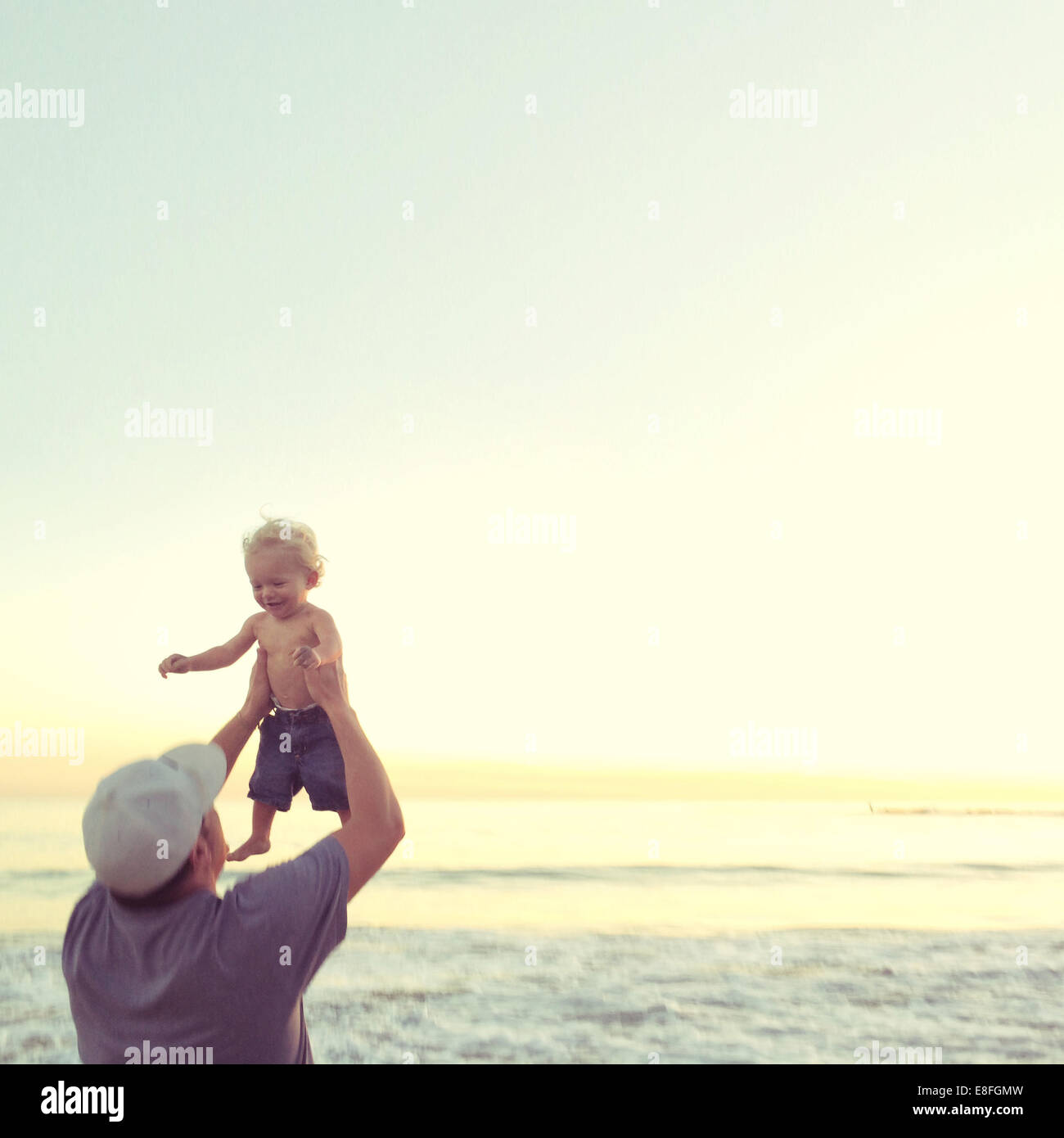 Father lifting his baby son in the air at the beach, california, america, USA - Stock Image