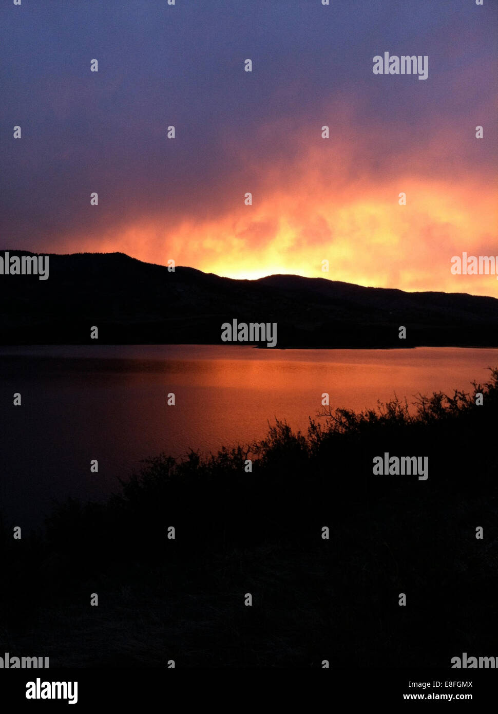 USA, Colorado, Larimer County, Fort Collins, Sunset in mountains across peaceful lake - Stock Image