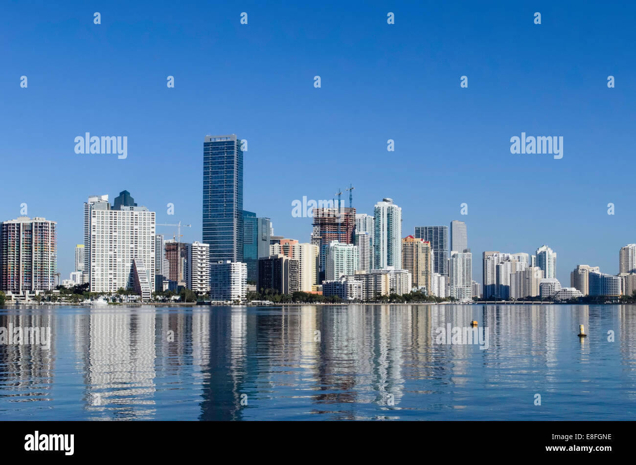Urban skyline reflecting in water - Stock Image