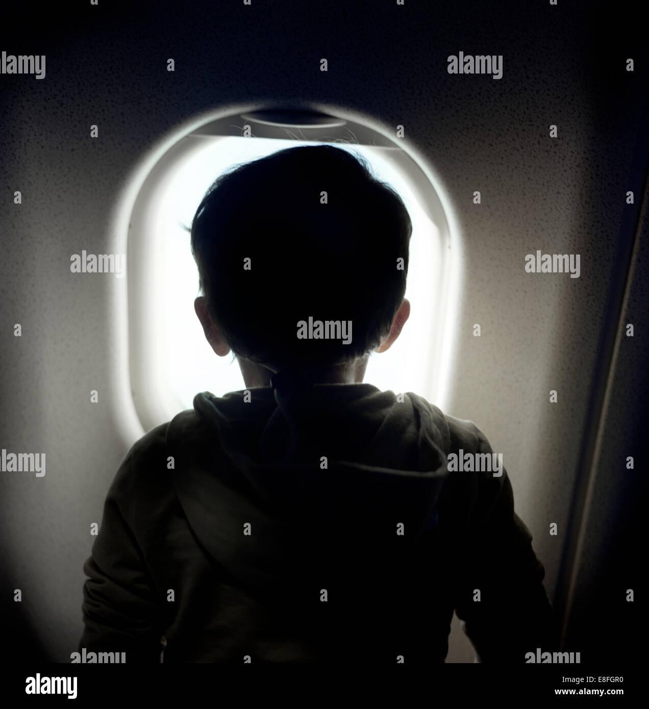 Boy looking through window on airplane - Stock Image