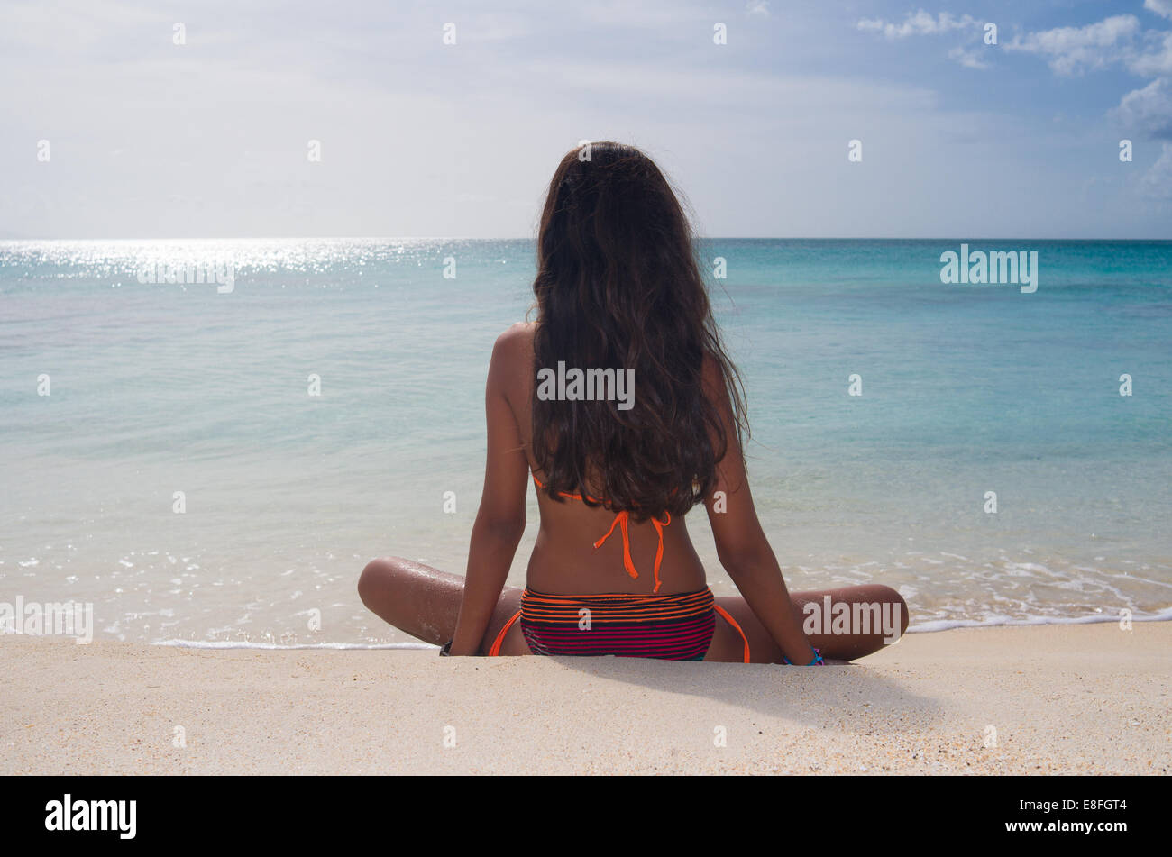 Rear view of girl sitting on Darkwood beach, Antigua, Caribbean Stock Photo