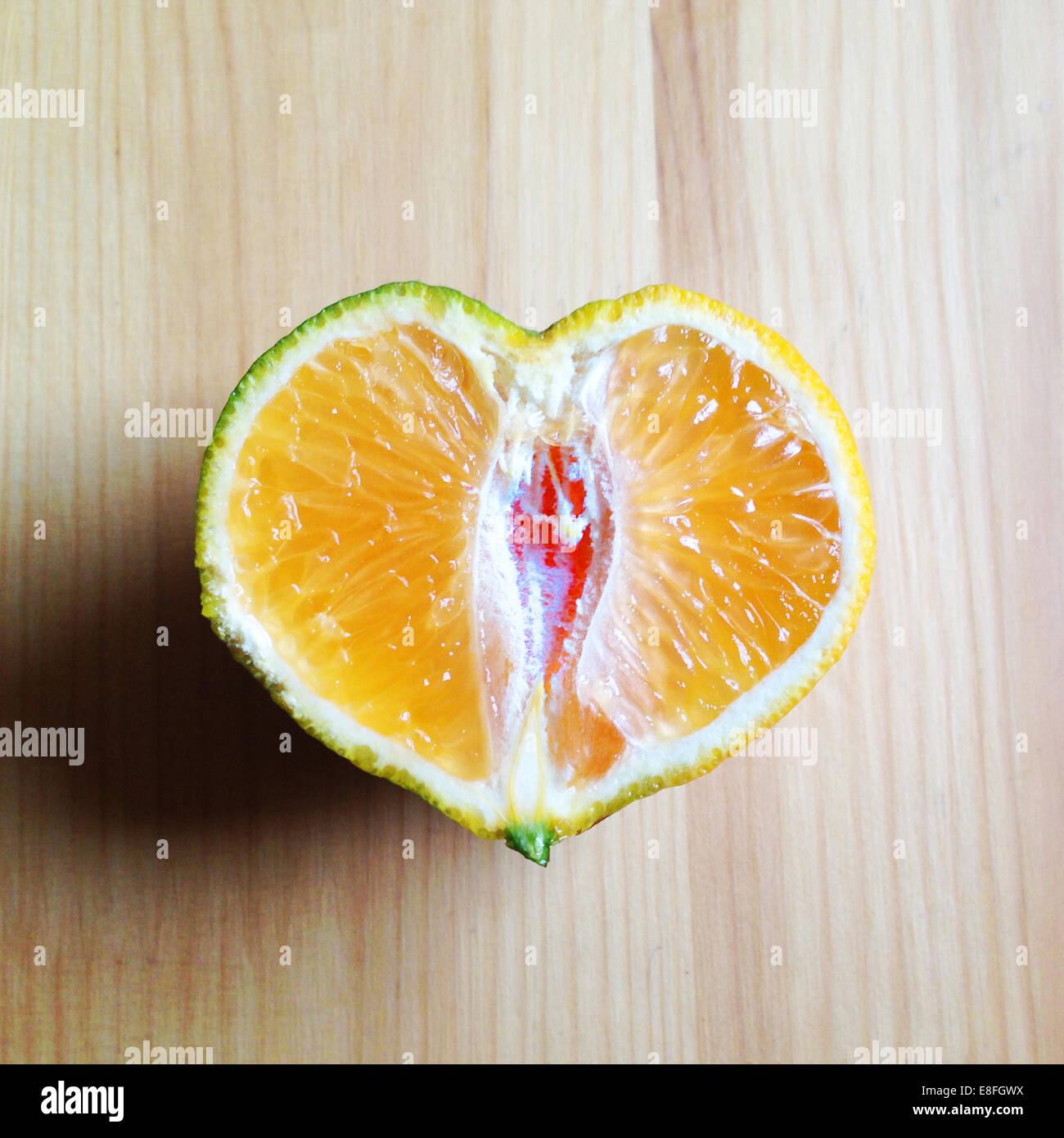 Heart shaped orange cut in half - Stock Image